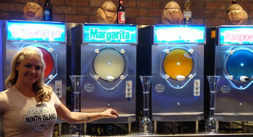 Sexy girl poses with frozen margarita machines at the Night Island Bar inside Downtown Grand