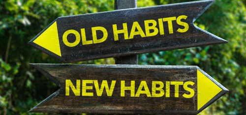 Trail sign with two arrows pointing to old habits and new habits