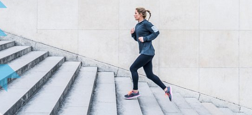 woman jogging up a flight of stairs outside