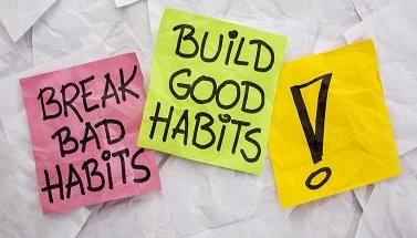 three post-it notes on wall one saying 'break old habits' the other saying 'build good habits'